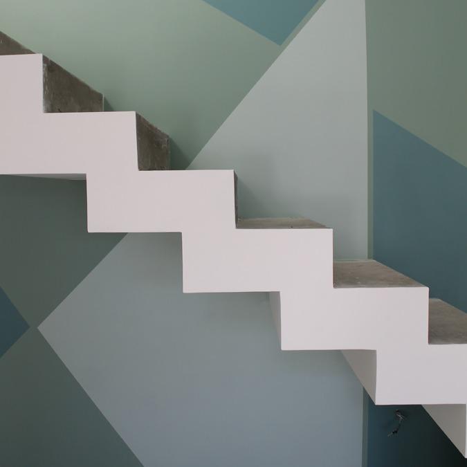 foto di decorazione su parete con campire triangolari nei toni del verde e scala moderna bianca usata nella sezione Colore per i tuoi Clienti di Bludiprussia