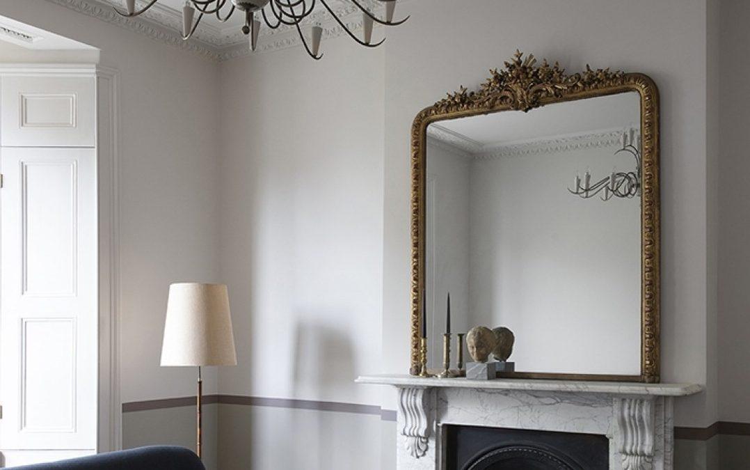 soggiorno con pareti bianche camino specchio divano bludiprussia
